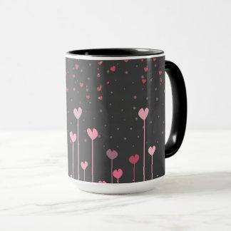 Corazones rosados en la taza de café negra del