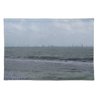 Costa de la playa con los veleros en el horizonte salvamanteles