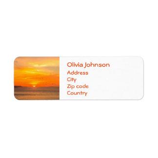 Costa de la puesta del sol con Sun anaranjado y Etiqueta De Remite
