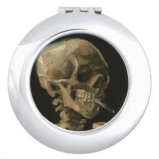 Cráneo esquelético con el cigarrillo ardiente de espejos de viaje