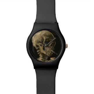 Cráneo esquelético con el cigarrillo ardiente de reloj de pulsera