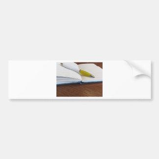 Cuaderno alineado espacio en blanco abierto con la pegatina para coche