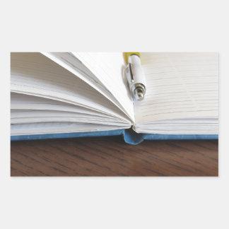 Cuaderno alineado espacio en blanco abierto con la pegatina rectangular