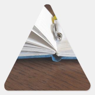 Cuaderno alineado espacio en blanco abierto con la pegatina triangular