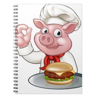 Cuaderno Cocinero del cerdo que sostiene la hamburguesa