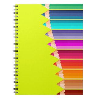 Cuaderno con los lápices del color