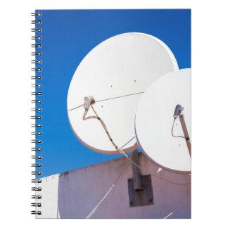 Cuaderno Dos antenas parabólicas blancas en la pared de la