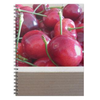 Cuaderno Frontera de cerezas frescas en fondo de madera