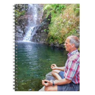 Cuaderno Hombre que se sienta en la roca meditating cerca