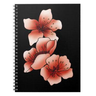 Cuaderno negro y flores de cerezo