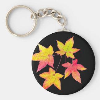 Cuatro hojas de otoño coloreadas en fondo negro llavero redondo tipo chapa