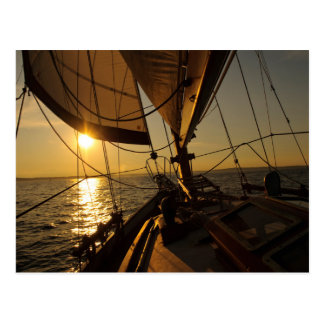 Cubierta del velero, dirigiendo en el sol poniente postal