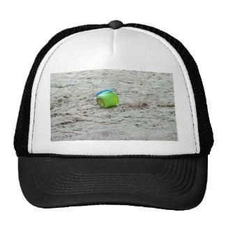 Cubo verde perdido en arena en la playa del verano gorras de camionero