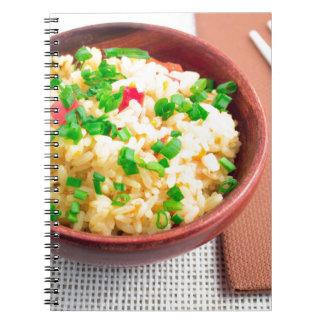 Cuenco de madera de arroz y de puerro cocinados cuaderno