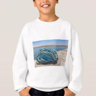 Cuerda azul en espiral del amarre en el agua en la sudadera