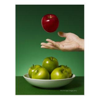 dé lanzar la manzana roja en el aire y el verde postal