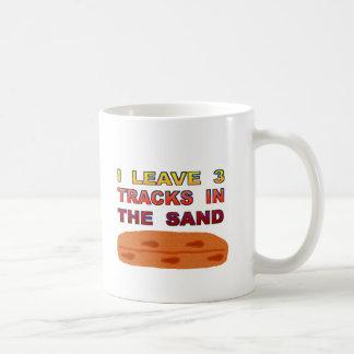 Dejo 3 pistas en la arena taza de café