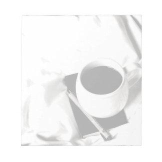 Desayuno blanco y negro de la taza de café en cama bloc de notas
