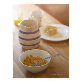 Desayuno comido mitad en la tabla de cocina postal