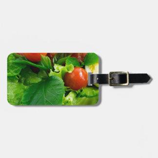 Detalle de una placa con los tomates de cereza, etiqueta para maletas
