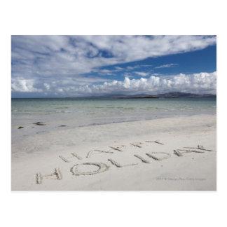 Día de fiesta feliz escrito en la playa de postal