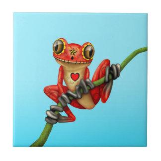 Día rojo de la rana arbórea muerta del cráneo del azulejo de cerámica