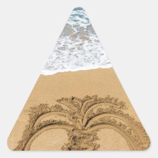 Dibujo de la palmera en la playa arenosa pegatina triangular