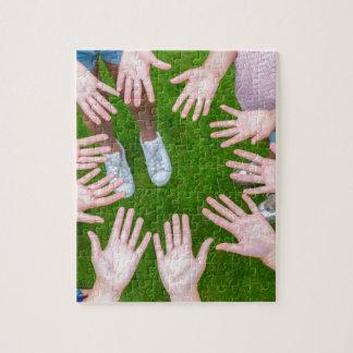 Diez brazos de niños en círculo con las palmas de puzzle