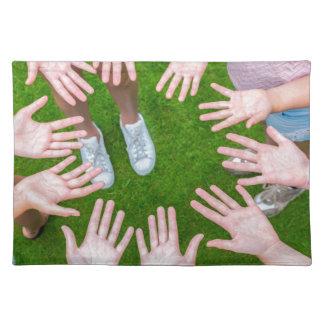 Diez brazos de niños en círculo con las palmas de salvamanteles