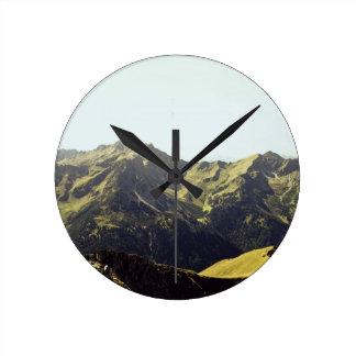 Diseño herboso del paisaje de la montaña reloj redondo mediano