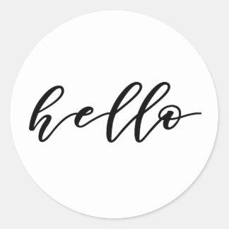 Diseño simple del hola en escritura hermosa de la pegatina redonda