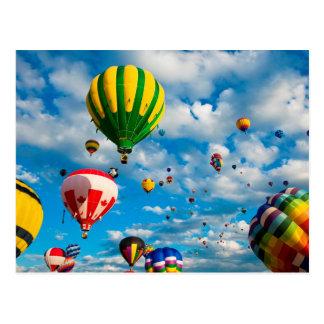 Docenas de globos del aire caliente en el cielo postal