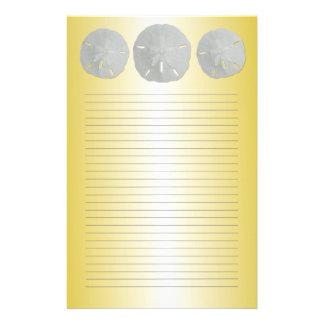 Dólares de arena en el papel de escribir alineado