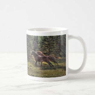 Dos caballos del rancho que corren en bosque tazas de café