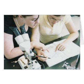 Dos chicas con el microscopio tarjeta de felicitación