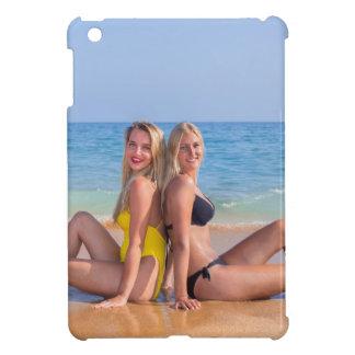 Dos chicas se sientan en la playa cerca de sea.JPG