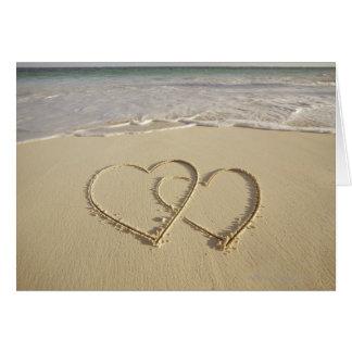 Dos corazones sobrepuestos dibujados en la playa felicitaciones