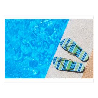 Dos deslizadores de baño en el borde de la piscina postal