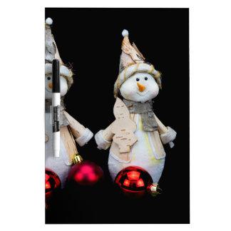 Dos estatuillas de los muñecos de nieve con las pizarra blanca