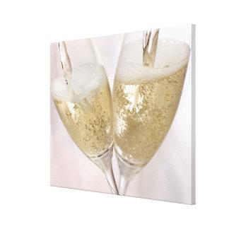 Dos flautas de champán que son llenadas de impresión en lienzo