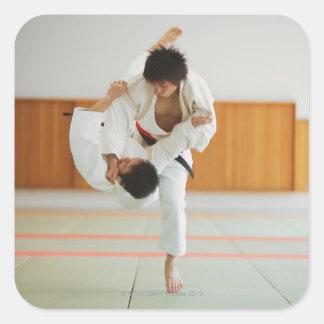 Dos hombres que compiten en un partido del judo pegatina cuadrada