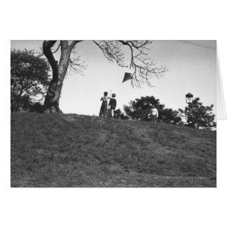 Dos muchachos que vuelan la cometa en la colina tarjeta de felicitación