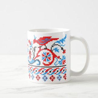 Dos pájaros coloridos del punto de cruz que casan taza de café