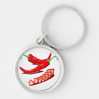 Dos pimientas de chile rojo una cortadas también llaveros