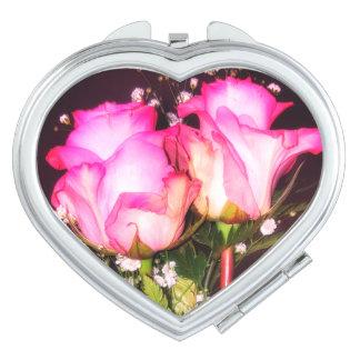 Dos rosas rosados con el espejo del acuerdo de la espejos de maquillaje