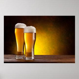 Dos vidrios de cervezas en una tabla de madera póster