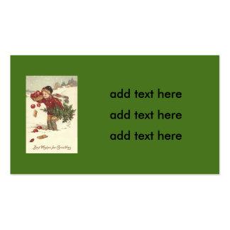 El árbol de navidad del muchacho presenta nieve de tarjetas de visita