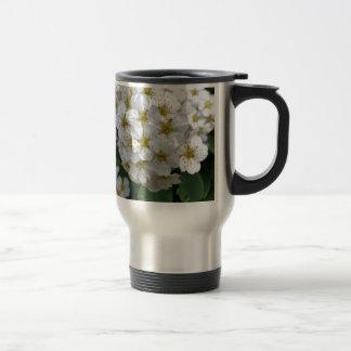 El brillar intensamente de las flores blancas taza de viaje