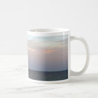 El brillar intensamente se nubla sobre el mar taza de café