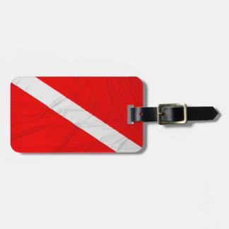 El buceador arrugado abajo señala por medio de una etiquetas para maletas